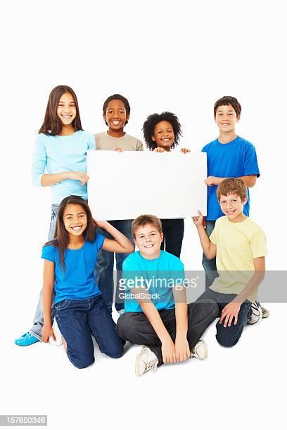 Happy children holding placard against white