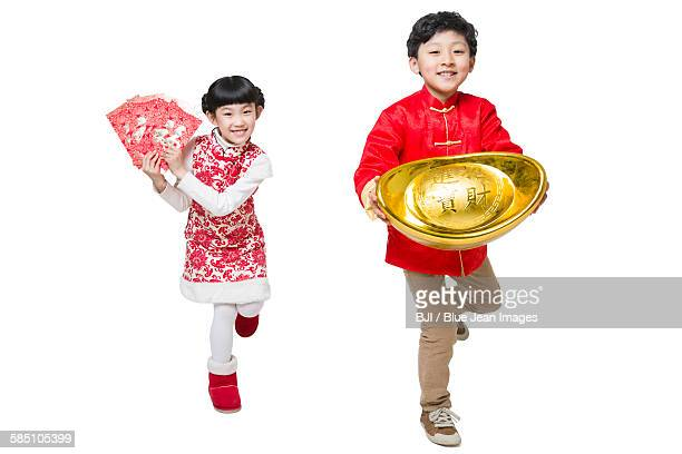 Happy children holding red envelopes and Chinese traditional currency yuanbao