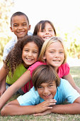 Group Of Children Piled Up In Park smiling at camera