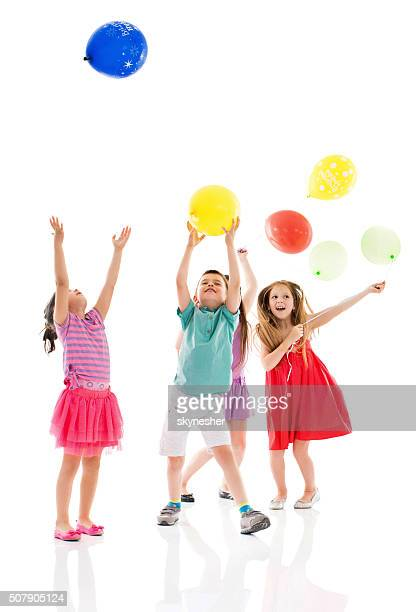 Happy children playing with balloons together.