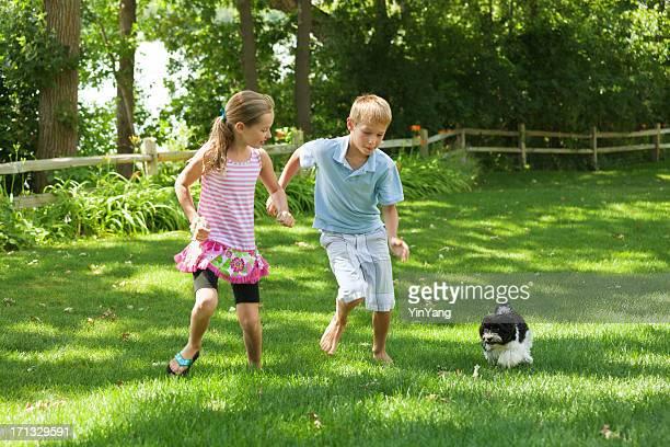 Glückliche Kinder spielen mit Haustier-Hund im Garten