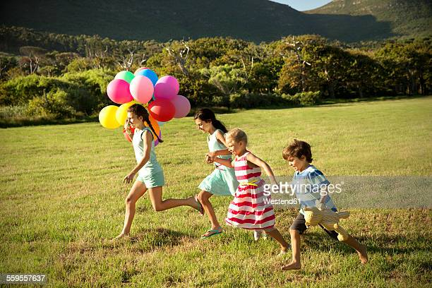 Happy children running with balloons on meadow