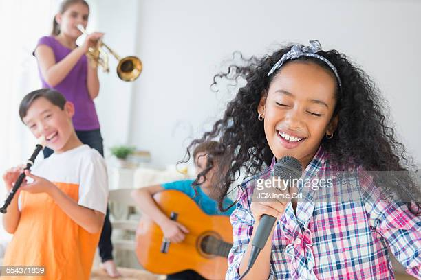 Happy children singing and playing music