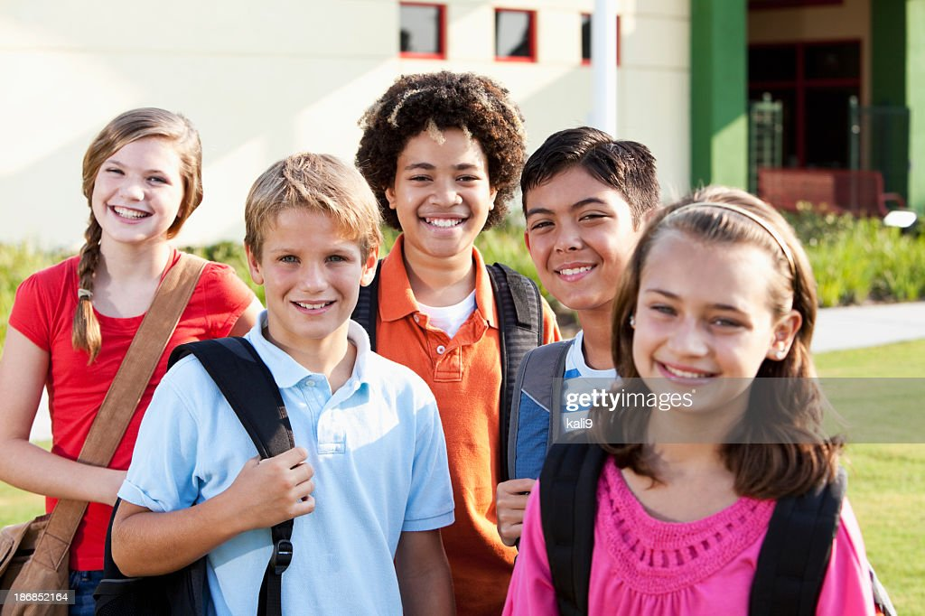 Enfants debout à l'extérieur de l'école avec bookbags : Photo