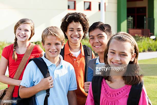Happy children standing outside school with bookbags