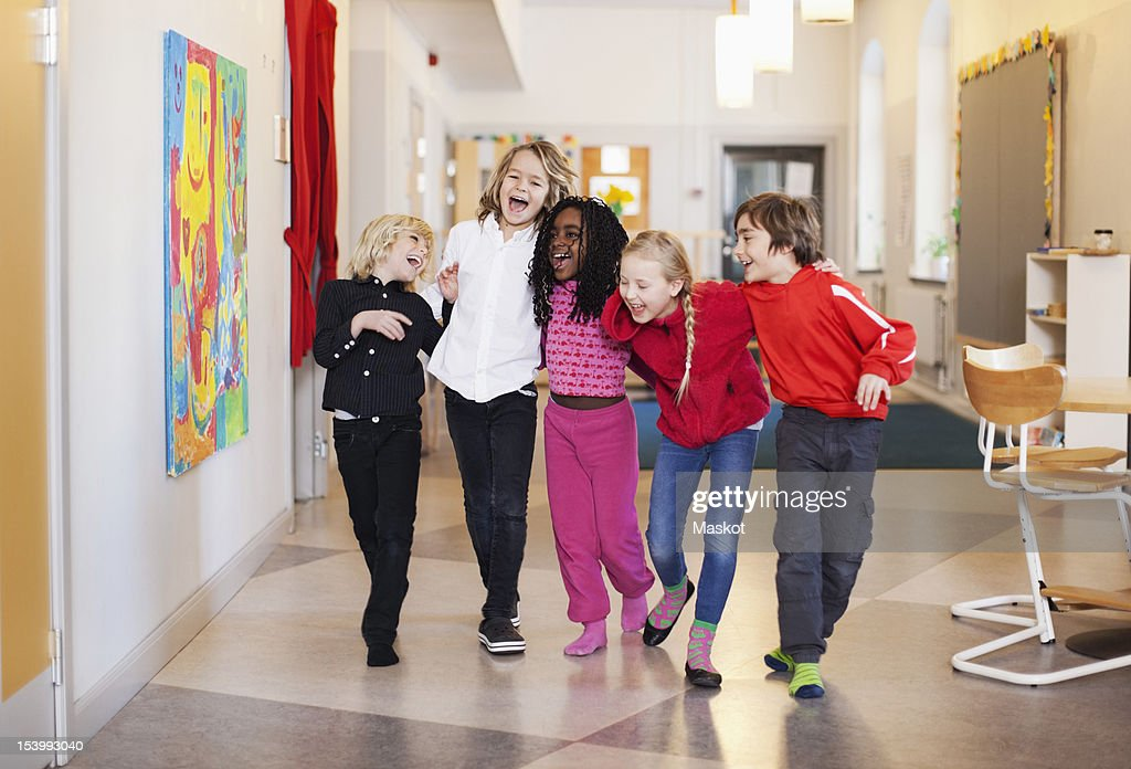 Happy children walking in school corridor : Stock Photo