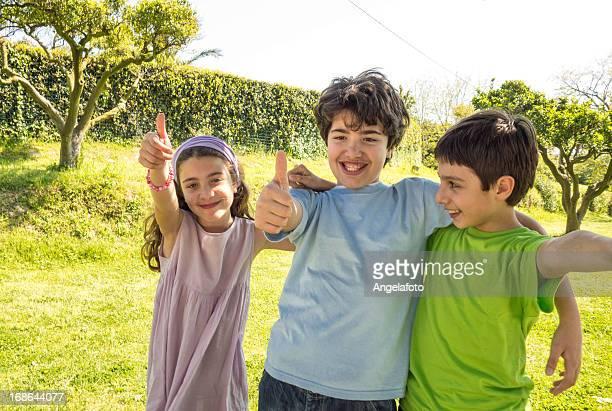 Glückliche Kinder mit Daumen hoch im Freien