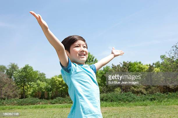Happy Chinese boy enjoying the moment in a park