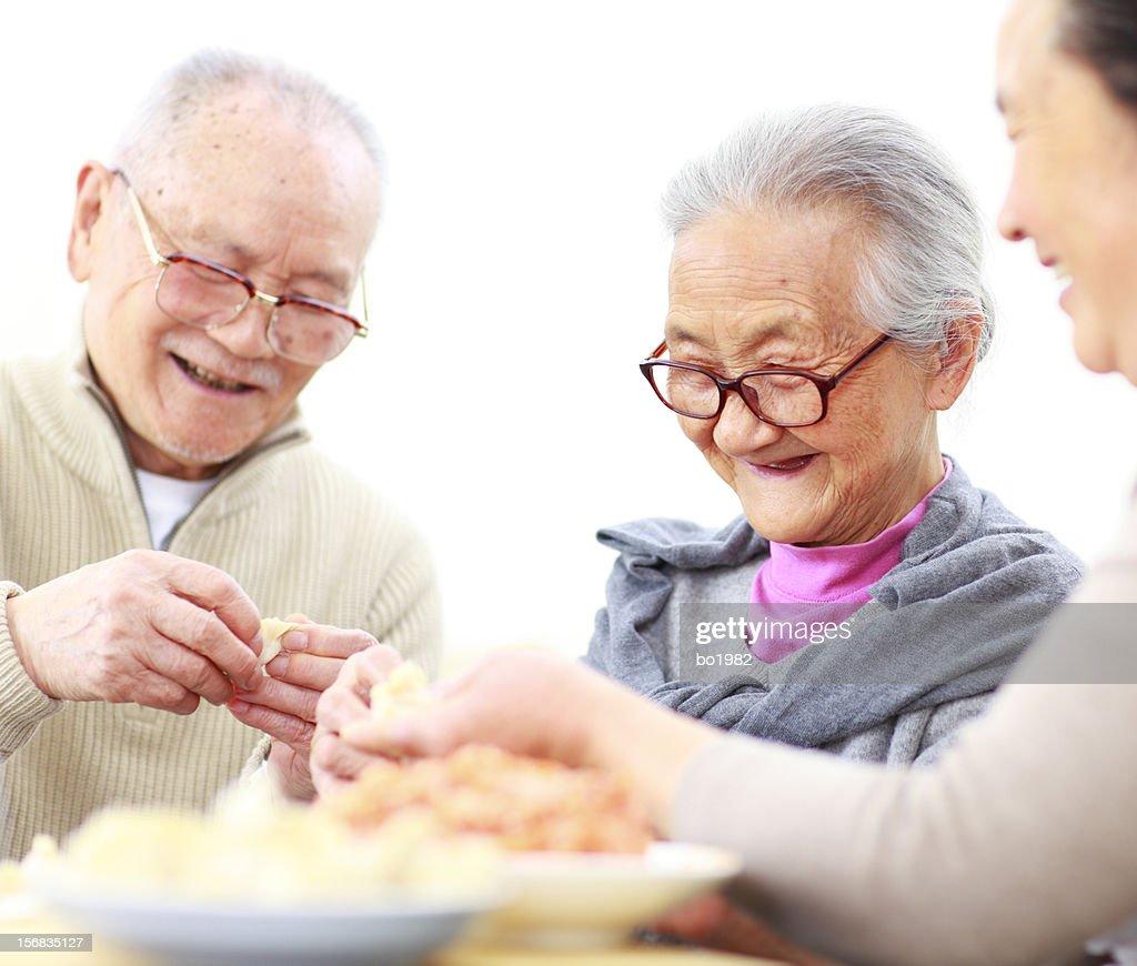 happy chinese family preparing dumplings in home : Stock Photo