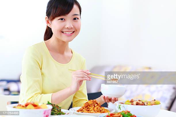 happy Chinese young woman have dinner in home