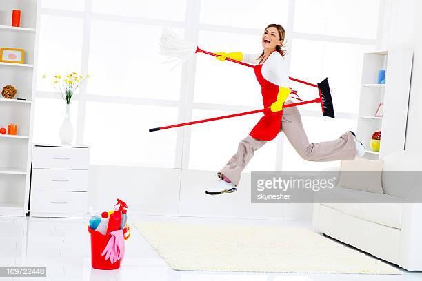 Femme de ménage heureux sautant à terminer une course de faire le ménage