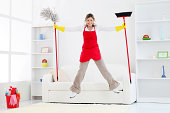 Happy cleaning lady jumping with broom and mop.