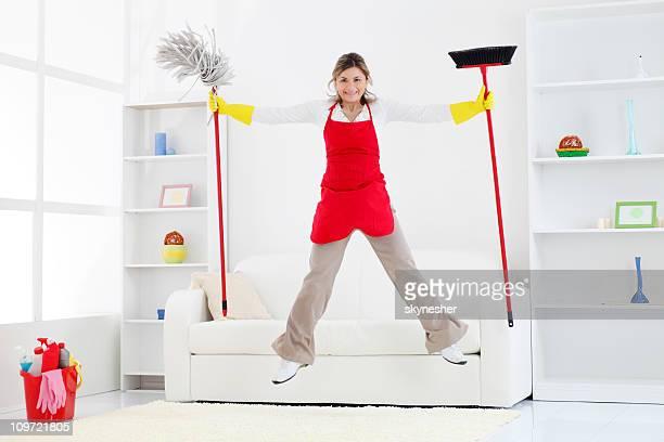 Felice Donna delle pulizie saltando con scopa e mop.