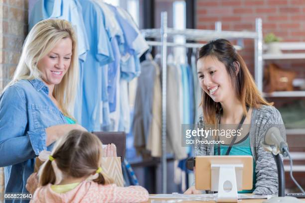 Happy clothing store manager assists young customer