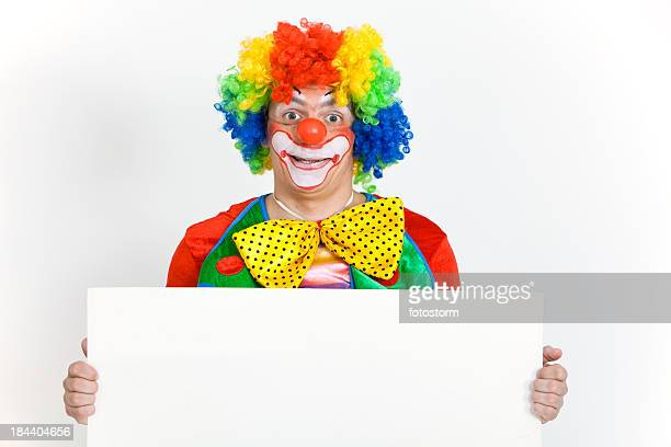 Happy clown holding blank banner with copy space