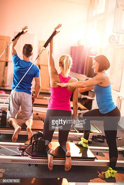 Happy coach helping athletes in doing exercises on Pilates machines.