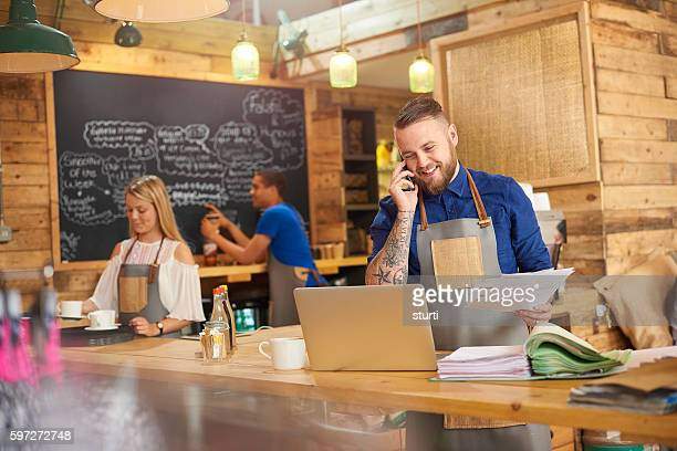Happy Coffee shop owner on the phone