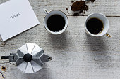 Happy coffee time. Top view of two coffee cups, italian coffee maker-moka and white card with 'Happy' text