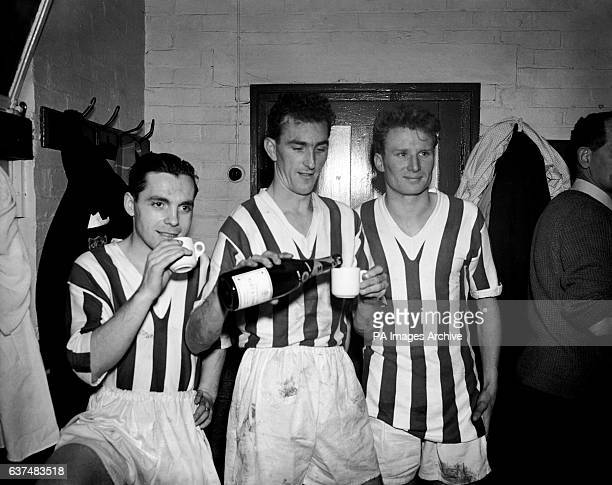 Happy Colchester players Sam McLeod left John Evans centre and John Wright right celebrate their draw against Arsenal with champagne in the dressing...