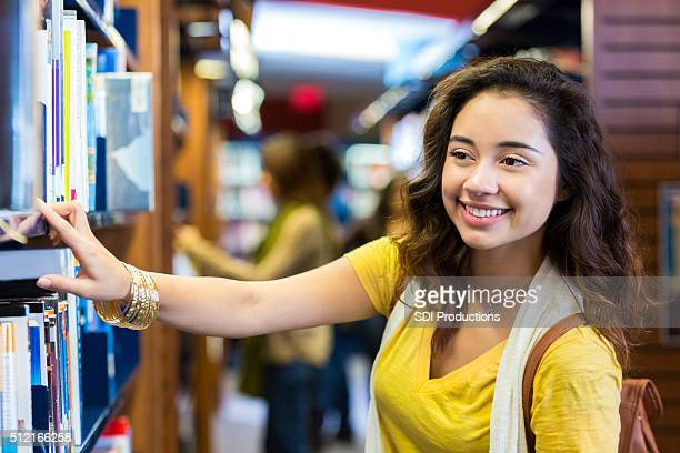 Happy college girl searching for book in public library