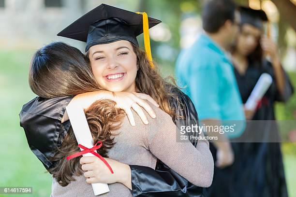 Happy college grad hugs her mom