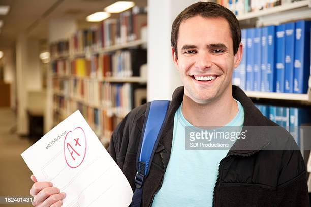 Happy College Student in Library Holding Excellent Grade on Exam