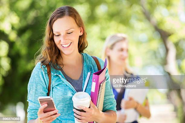 Happy college student texts friend before class