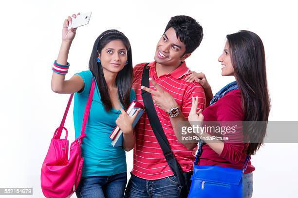 Happy college students taking selfie through smart phone against white background