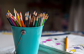 Bucket of color pencils with sketching notebook.
