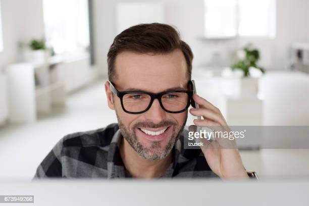 Happy computer programmer working in an office