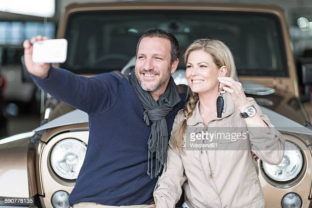 Happy couple at car dealership taking selfie in front of new car