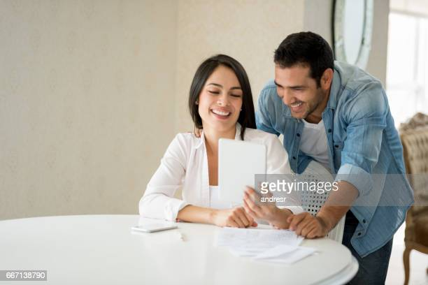 Happy couple at home online on a tablet computer