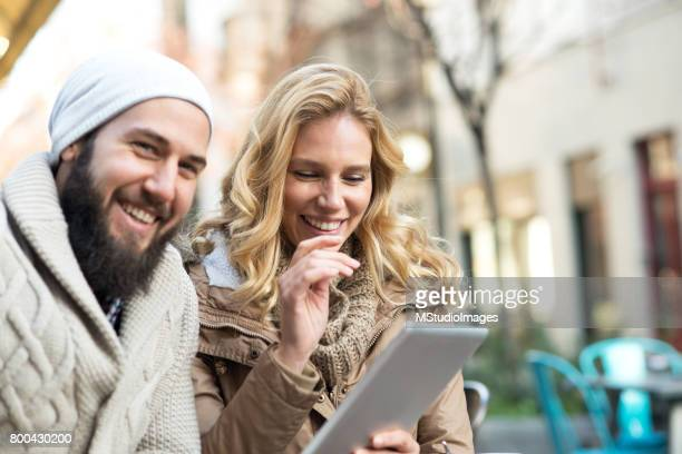 Happy couple at the bar using digital tablet