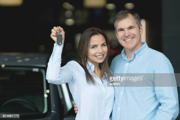 Happy couple at the dealership holding keys to their new car
