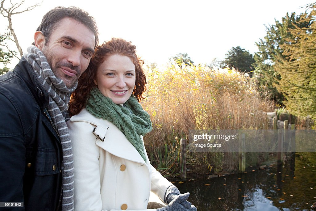 A happy couple beside the water in dulwich park : Stock Photo