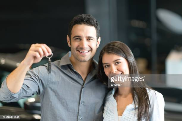 Happy couple buying a car at the dealership and holding the keys