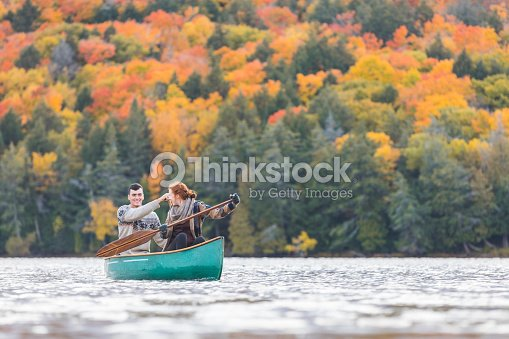 Happy couple canoeing in a lake in Canada : Stock Photo