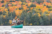 Happy couple canoeing in a lake in Canada. There are many trees on background with colourful leaves during autumn. They are young and happy, enjoying a canoe trip together. Wanderlust and nature conce
