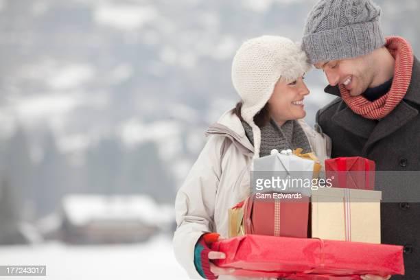 Feliz pareja transporte de Navidad y regalos en la nieve