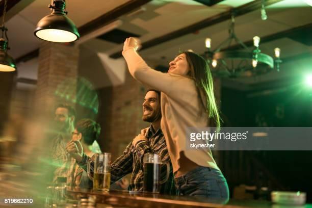 Gelukkige paar vieren tijdens het kijken naar een voetbalwedstrijd in een bar.