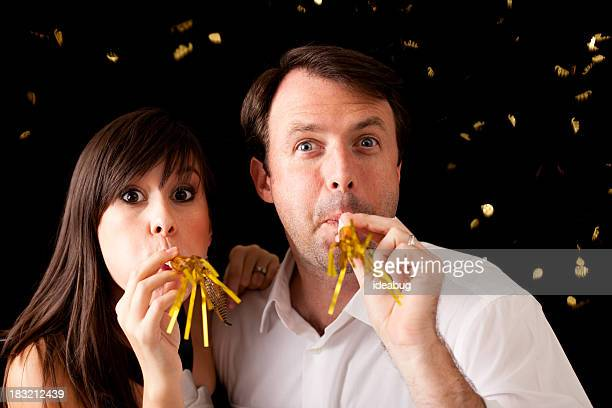 Happy Couple Cheering and Celebrating New Year with Noise Makers
