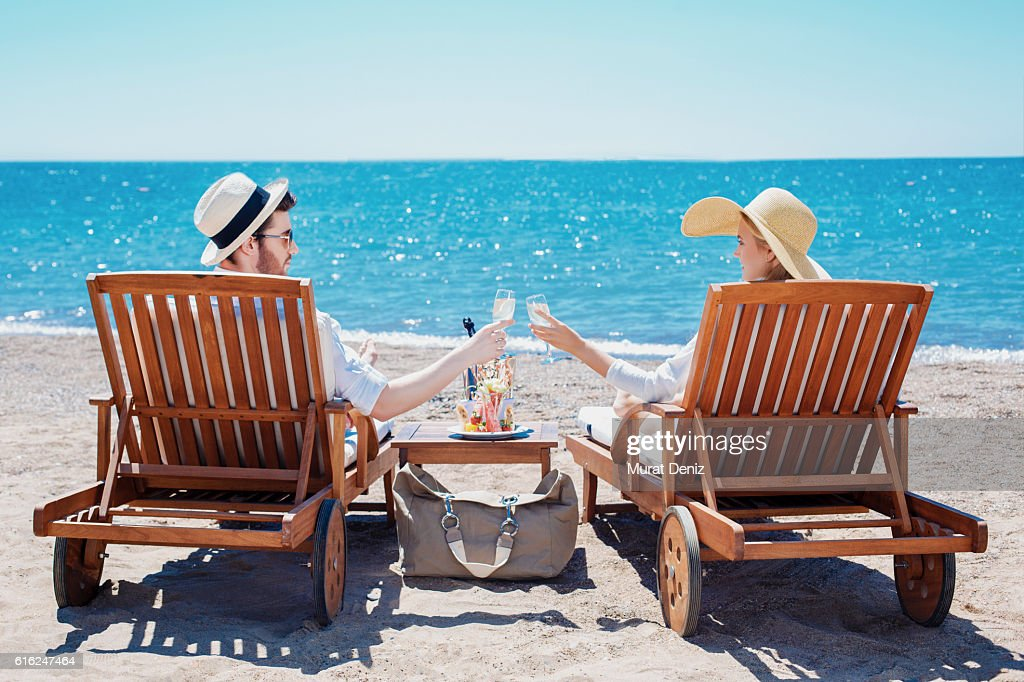 Happy couple clinking their glasses while relaxing on the beach : Stock-Foto