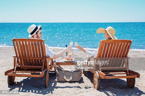 Happy couple clinking their glasses while relaxing on the beach : Stock Photo
