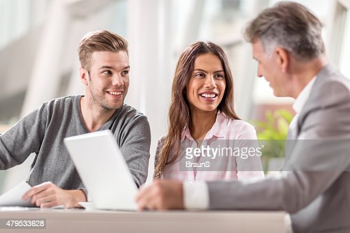 Happy couple cooperating with financial advisor in the office.