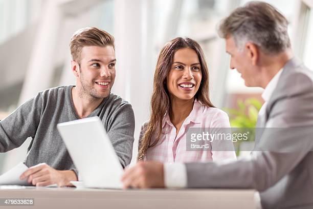 couple heureux de collaborer avec le Conseiller financier au bureau.