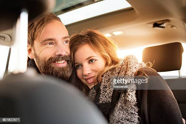 Happy couple cuddling in a car