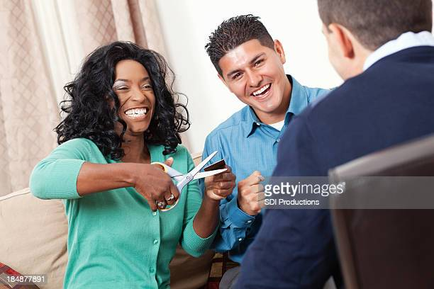 Happy couple cutting up credit card with financial advisor