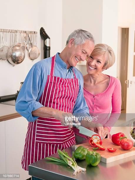 Glückliches Paar Schneiden Gemüse in der Küche