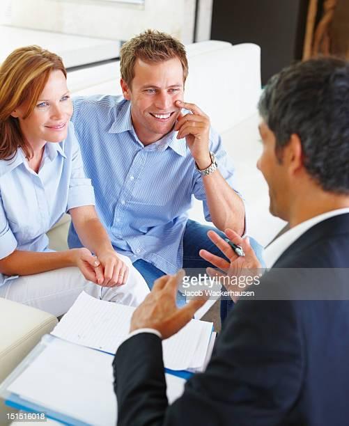 Glückliches Paar diskutieren mit Berater finanzielle