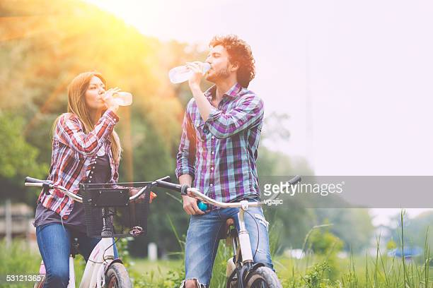 Happy Couple Drinking Water After Riding Bicycles.